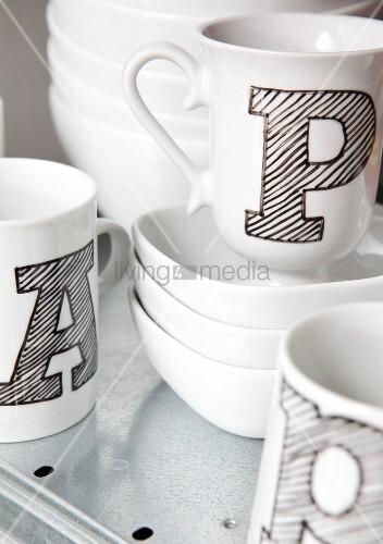 weiße Tassen mit schwarz schraffierten Buchstaben