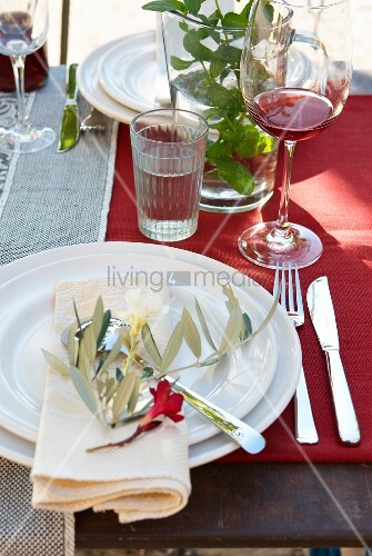 Place settings with olive sprig and flower on red tablecloth