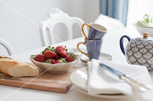 Table set with strawberries, baguette and blue-patterned crockery
