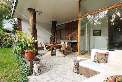 Bungalow with tree trunks integrated into roofed terrace