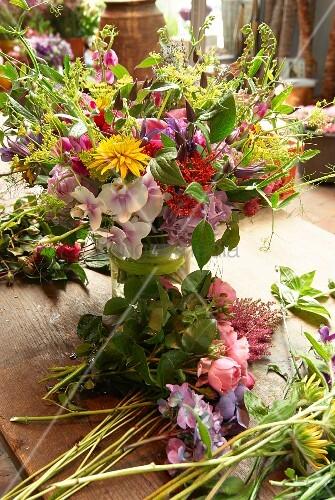 Bunter Sommerblumenstrauß in Glasvase neben Schnittblumen auf Holztisch