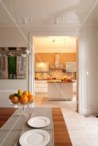 Esszimmer mit Deckenstuck und Blick in beleuchtete Küche
