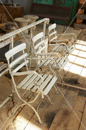 White vintage garden chairs on rustic board floor