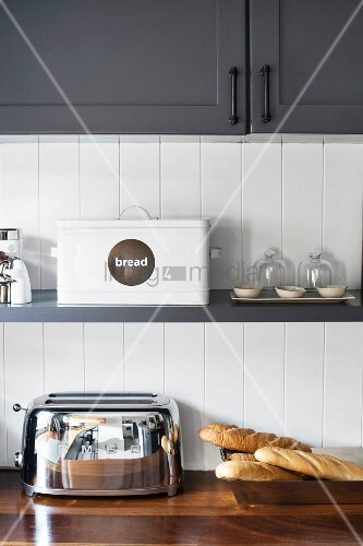 Shelf below wall-mounted cupboards in grey and white country-house kitchen