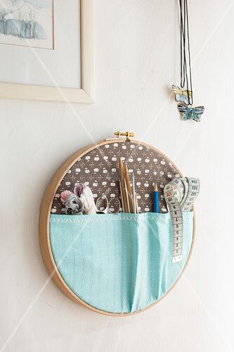 Organiser for sewing utensils in embroidery frame on wall