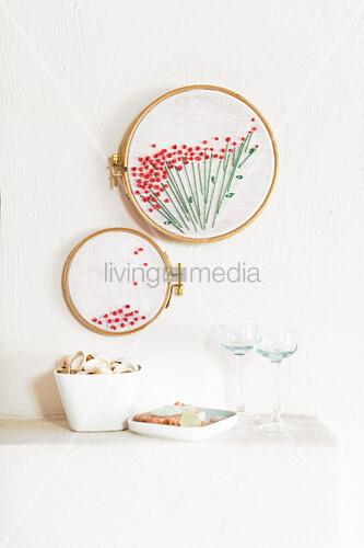 Stickringe mit aufgesticktem Blütenmotiv an der Wand