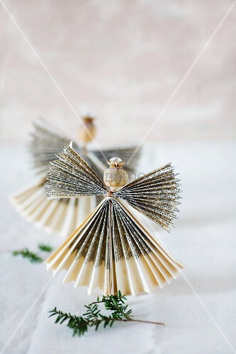 Angel made from folded paper with head made from poppy seed capsule