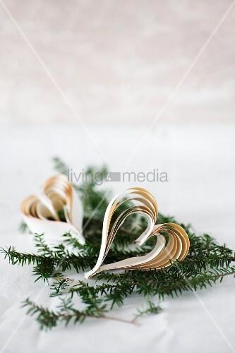 Herzen aus zusammengehefteten Papierstreifen auf Tannenzweigen