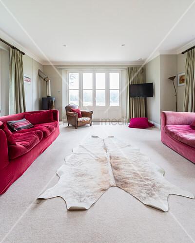 Cowhide rug between two red sofas in living room