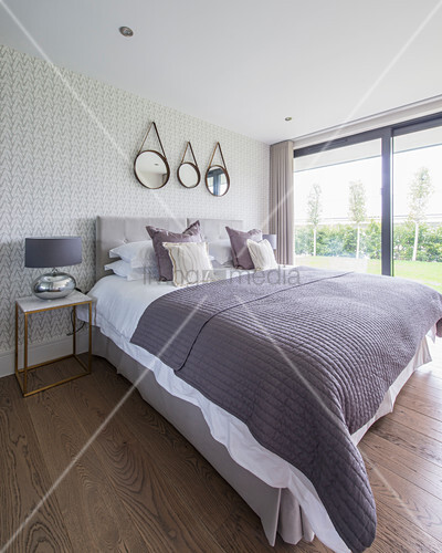 Elegant bedroom in purple and grey with glass wall