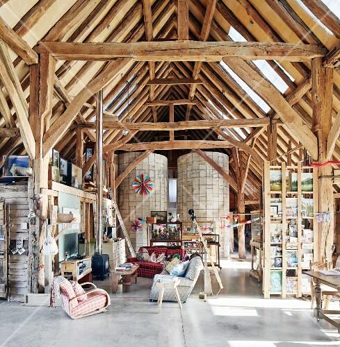 Offener Wohnraum in umgebauter Scheune mit rustikaler Dachkonstruktion