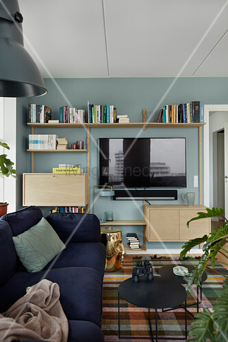 TV and shelves mounted on blue wall in living room