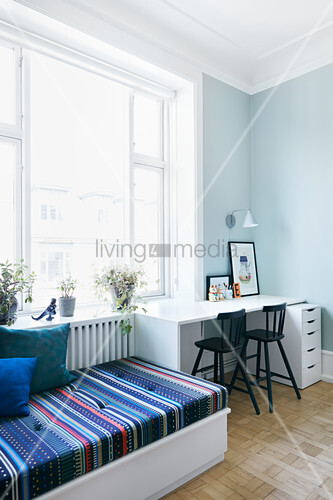 Day bed next to desk with two chairs below window