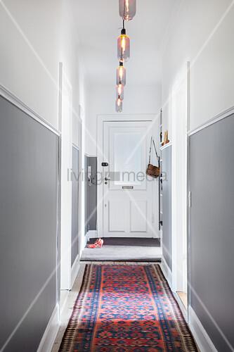 Zweifarbig gestrichener Flur mit langem Teppich im Altbau