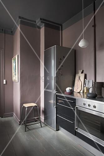 Auberginefarbene Wände in dunkler Küche mit schwarzen Fronten
