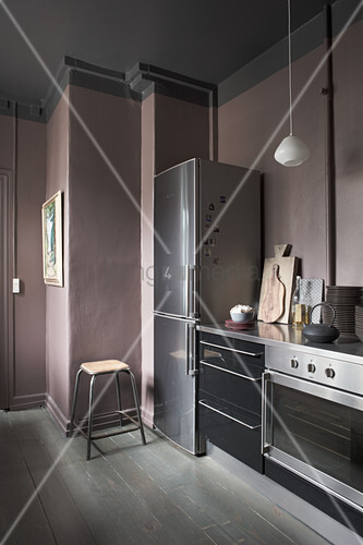 Pale lilac-grey wall in dark kitchen with black cabinets