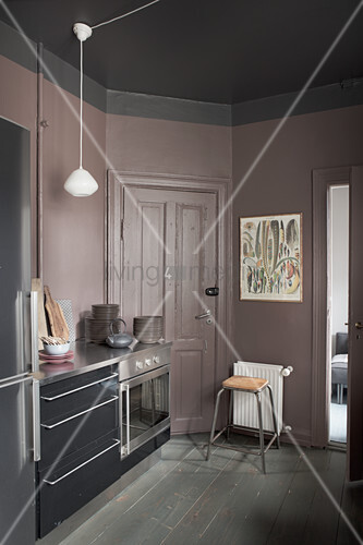 Lilac-grey walls in dark kitchen with black cabinets