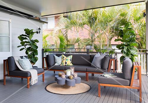 Sitzgruppe aus Holz mit grauen Polstern auf der Veranda