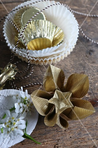 Gold origami flowers next to paper cake cases and bakers' string