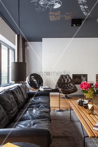 Black leather sofa in vintage living room with painted ceiling