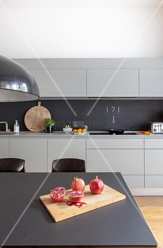 Aufgeschnittener Granatapfel auf dem Esstisch in grauer Küche
