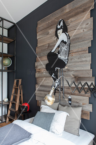 Industrial-style bedroom with artwork painted on wooden boards above bed