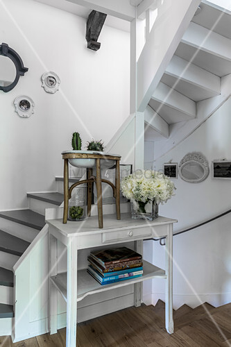 Books and flower arrangement on white table at foot of staircase