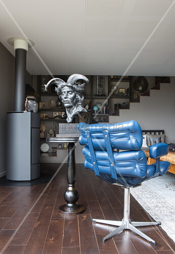 Bust on side table next to blue leather armchair in living room