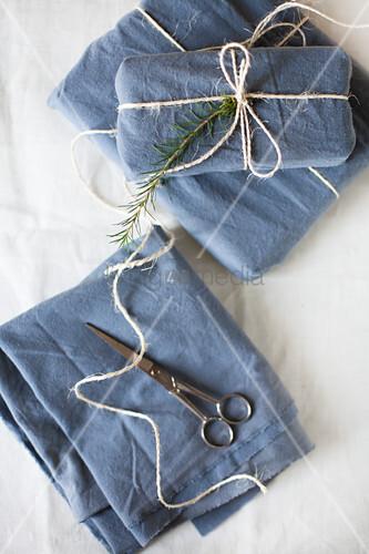 In blauen Stoff verpackte Geschenke mit Paketschnur