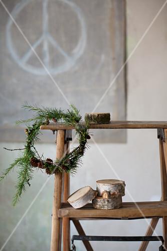 Kranz aus Lärchenzweigen mit Zapfen an einer alten Holzleiter