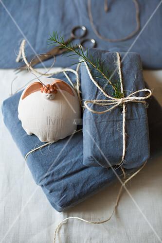 Getöpferter Engel auf in blauen Stoff verpackten Geschenken