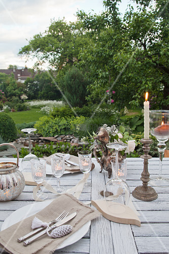 Table set with candle and tealight holder in garden