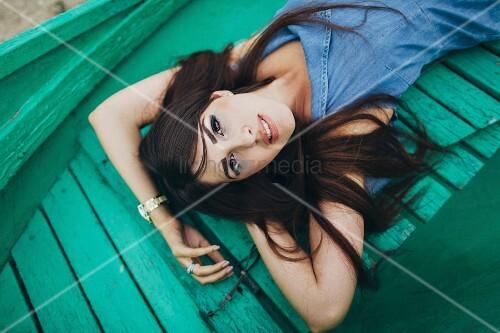Woman lying on green boardwalk