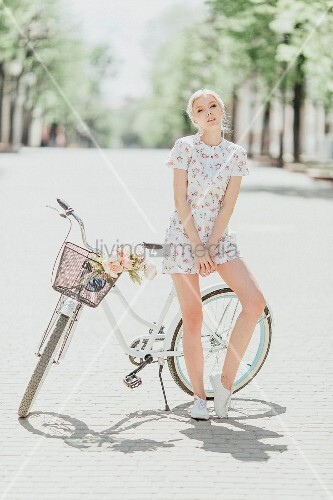 Young woman leaning against bicycle