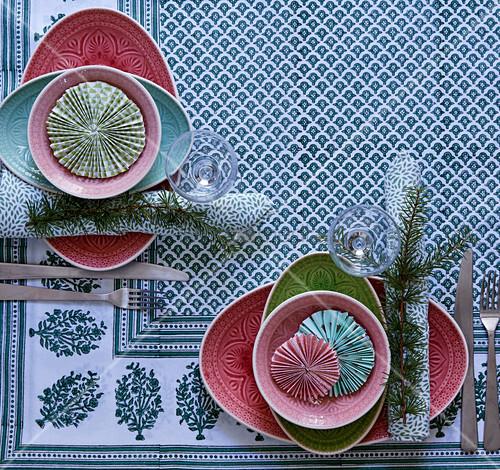 Gedeckter Tisch mit gemusterten Tellern und Rosetten als Deko