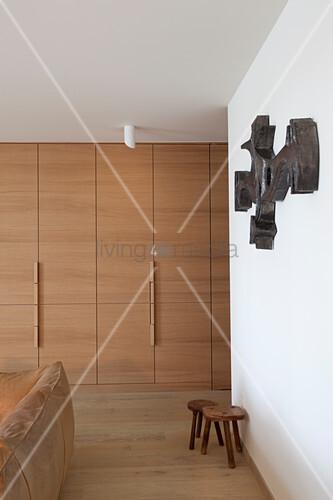 Raumhohe Einbauschränke, Holzhocker, Wandskulptur und Ledercouch im Wohnzimmer