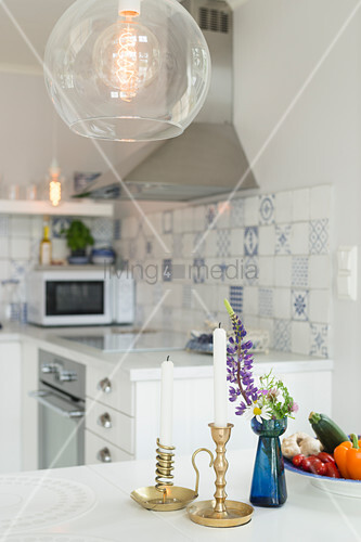 Candles and vase of flowers on dining table below spherical glass lamp in open-plan kitchen