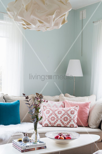 Scatter cushions on sofa and coffee table in corner of mint-green room