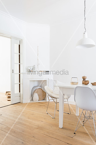 White dining area: dining table and classic chairs on wooden floorboards with disused fireplace in corner