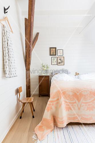 Apricotfarbene Tagesdecke auf dem Bett im ländlichen Schlafzimmer