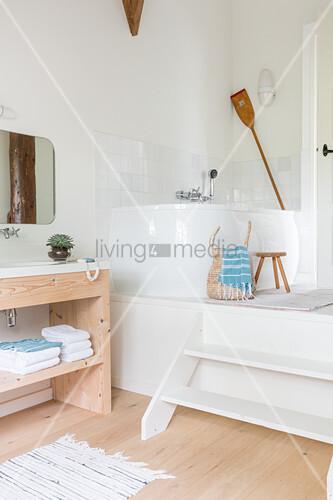 Corner bathtub on platform in bathroom in natural shades