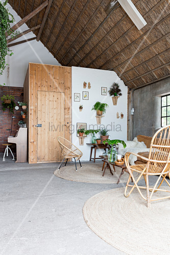 Wicker furniture and plants in living room in old, converted barn