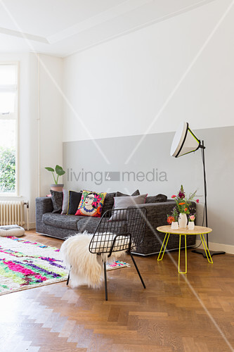Two-one wall behind sofa on herringbone parquet floor