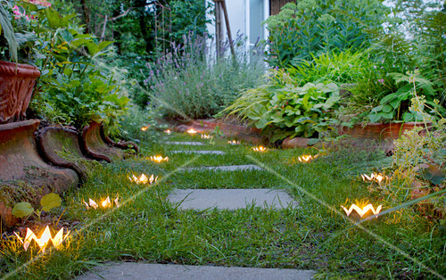 Crown-shaped candle lanterns hand-made from tin cans lining garden path