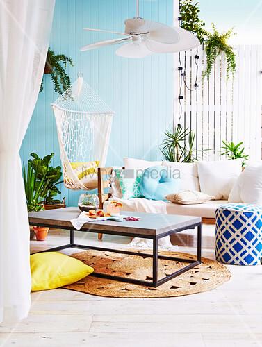 Somerfeeling auf der Terrasse mit blauer Bretterwand und Sofa