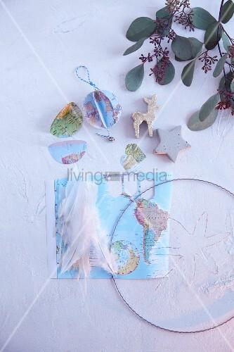 Weltkarte, Draht und Federn für selbstgemachte Weihnachtsdeko mit Friedensmotiven