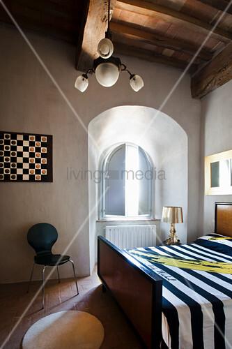 Doppelbett mit gestreifter Tagesdecke in renoviertem Schloss