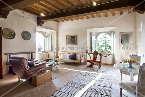 Wohnzimmer mit Ledersessel und Metallbank in renoviertem Schloss
