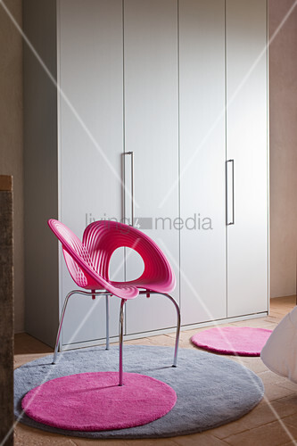 Pink designer shell chair in front of wardrobe