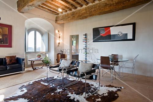 Klassikerstühle auf Kuhfellteppich in offenem Wohnraum